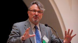 Alan Fisher speaking at a podium
